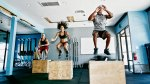Group fitness class working out with box jumps exercises
