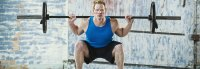 Fitness beginner starting strength workouts with a barbell squat exercise