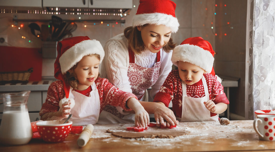Happy mother teaching her son and daughter to bake healthy holiday treats