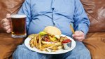 Overweight man eating junk food