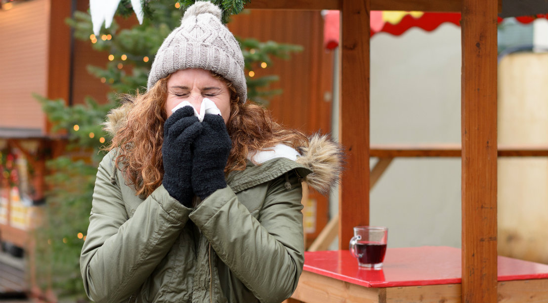 Woman sneezing in cold weather