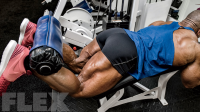 Bodybuilder Phil Heath doing a lying leg curl exercise