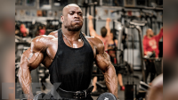 Bodybuilder Max charles working out his shoulder in a blank tank top in the gym