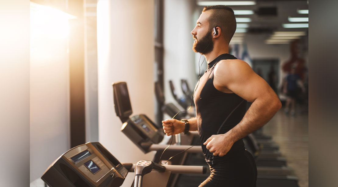 Man with muscular arms working out his cardio by running on a treadmill in the gym
