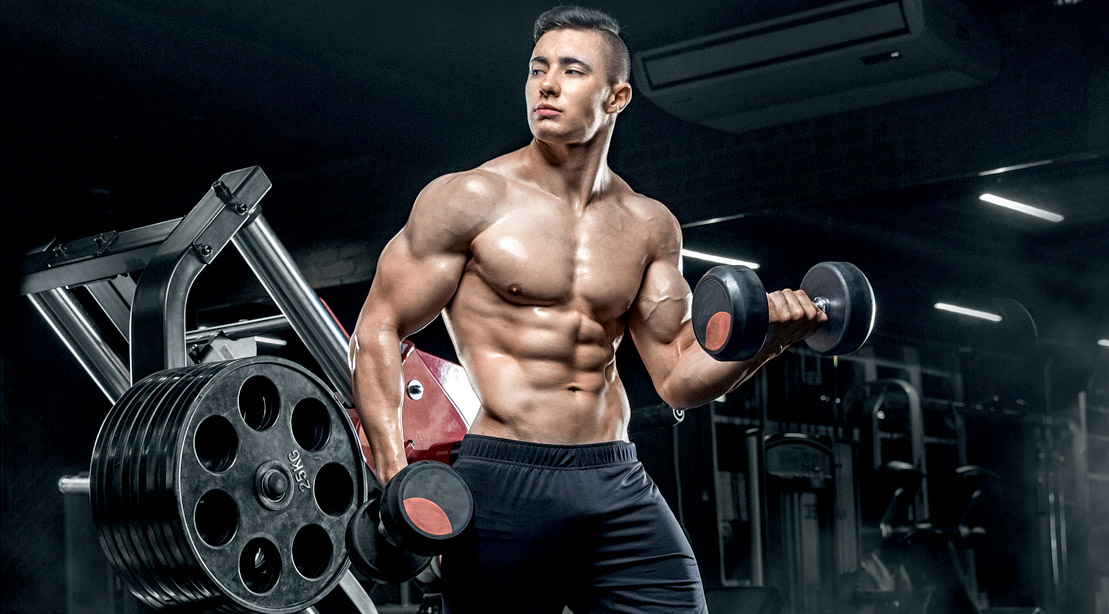 Lean muscular fitness model doing dumbbell bicep curls to get his body lean and muscular