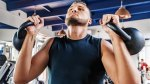 Man-With-Beard-and-Chin-Up-Holding-Two-Kettlebells
