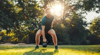 Man doing functional fitness workout in the park with a kettlebell swing exercise
