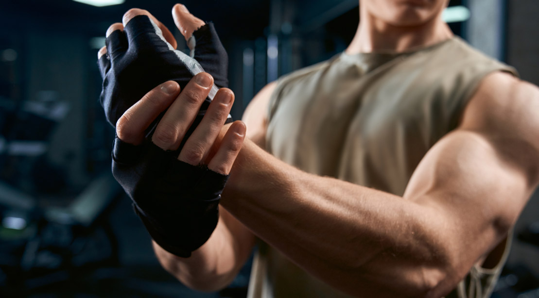 A fit young man making flexing his bicep muscles after an upper body exercises and workout