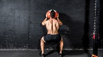 Physically fit man with a muscular back working out with a medicine ball pressed against a wall