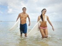 Couple carrying surfboards in the ocean