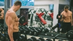 Fit Young Man Excersising With Dumb Bells At Gym