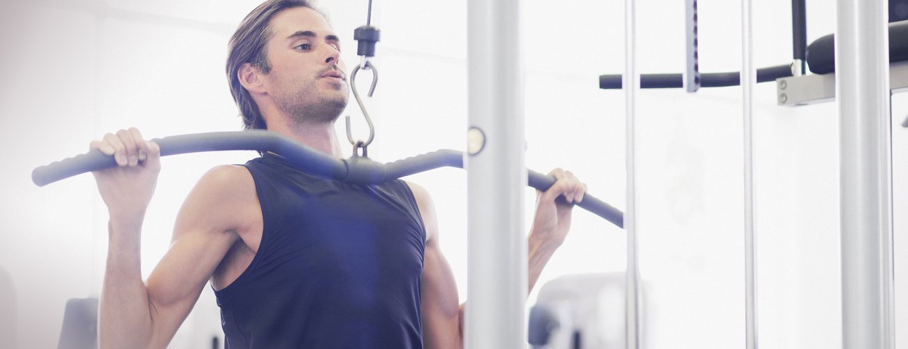 Skinny man working out at gym