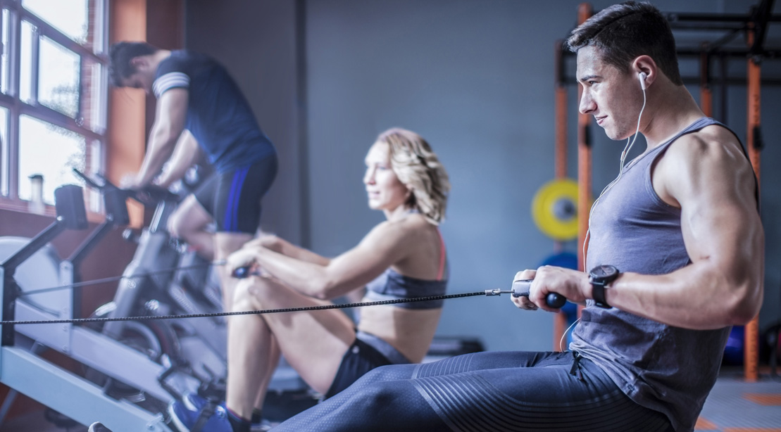 Young Man Exercising At Rowing Machine In Gym