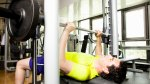Man bench-presses on Smith machine