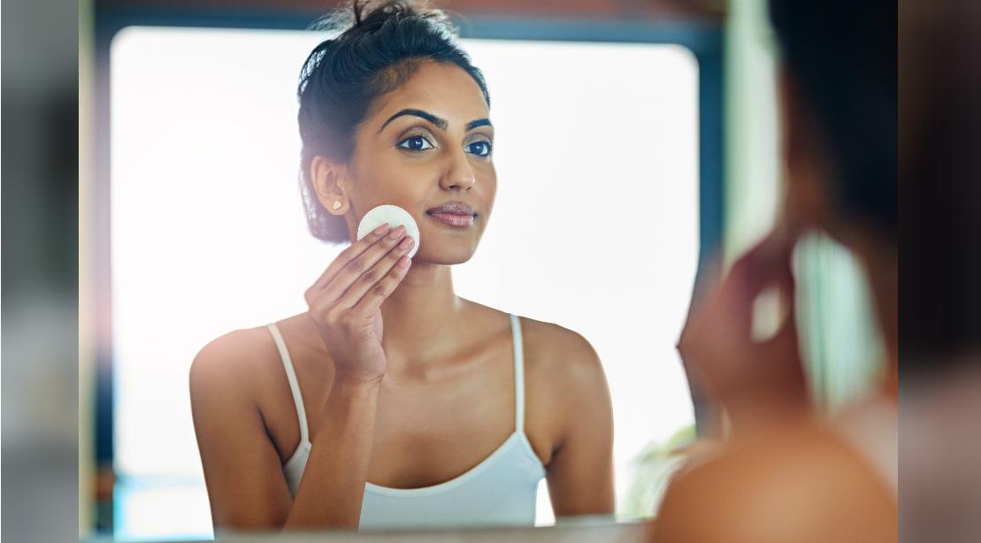 Woman Looking into Bathroom Mirror