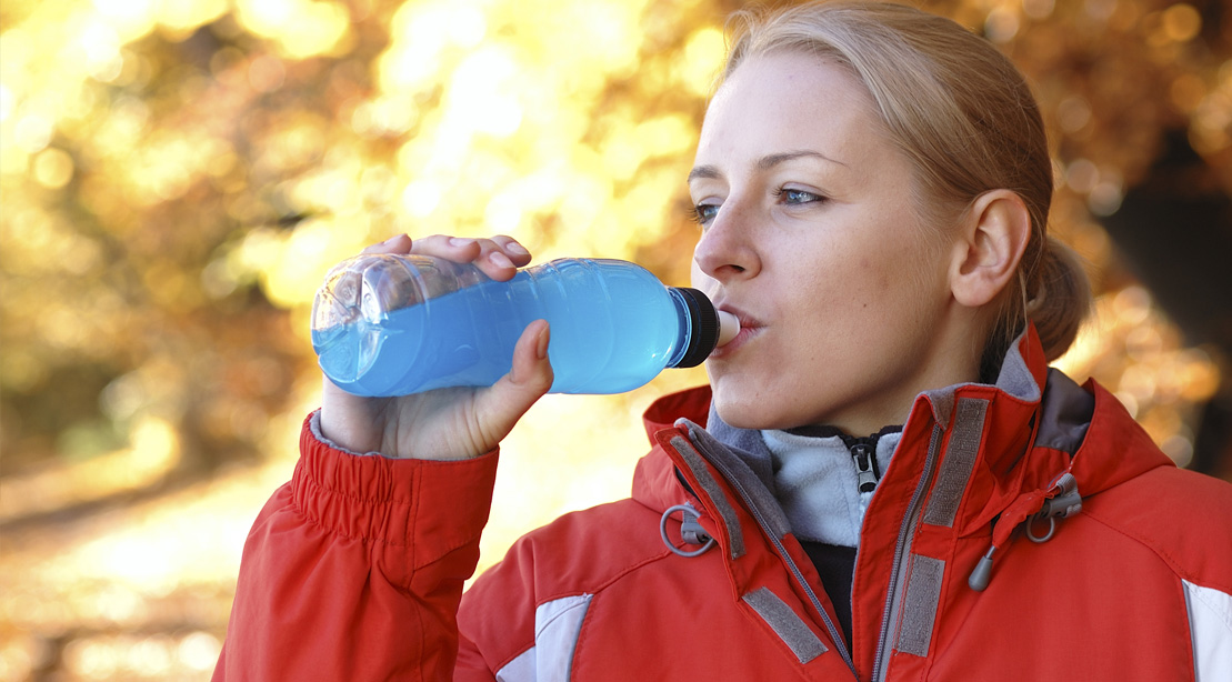 Female wearing red winter coat while drinking a blue sports drink