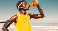 Fit runner drinking orange sports drink while running on the beach