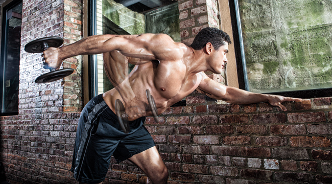 Fitness model and bodybuilder working out his arms with a tricep exercises the tricep kickbac