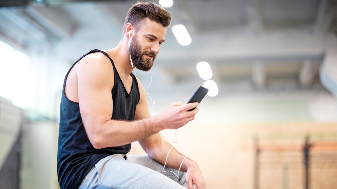 Man Looking at His Phone in the Gym