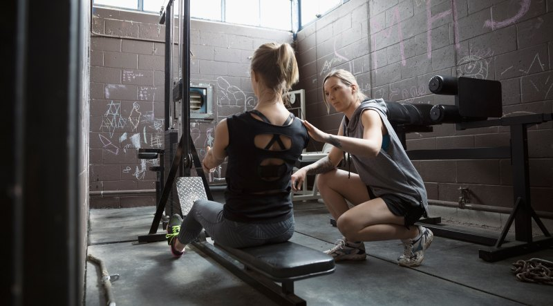 Personal Trainer Correcting Rowing Form