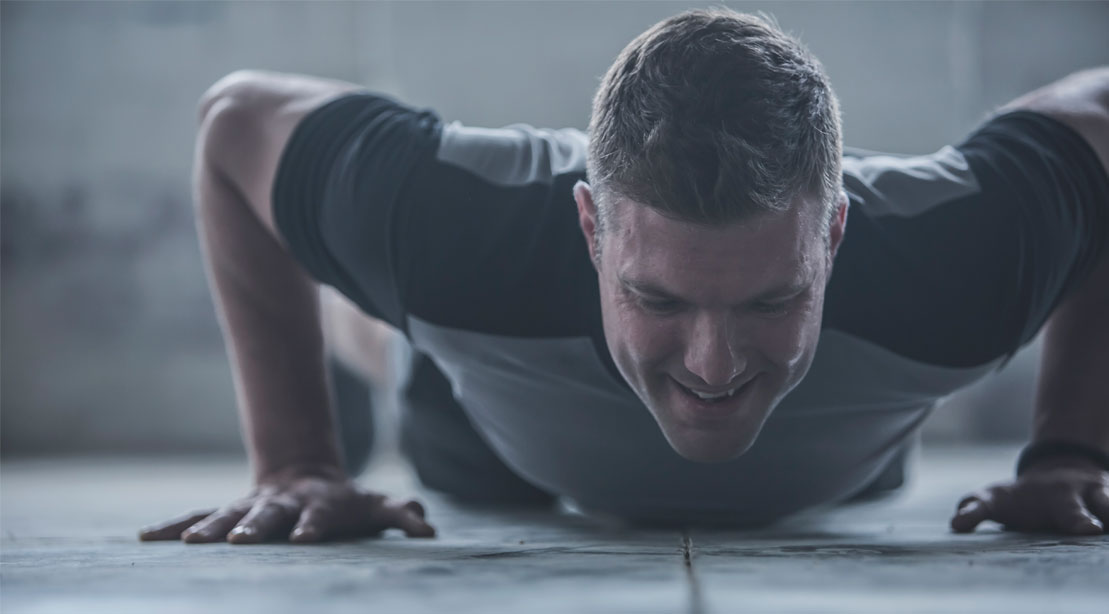Crossfitter struggling with a burpee and pushup while performing a EMOM workout