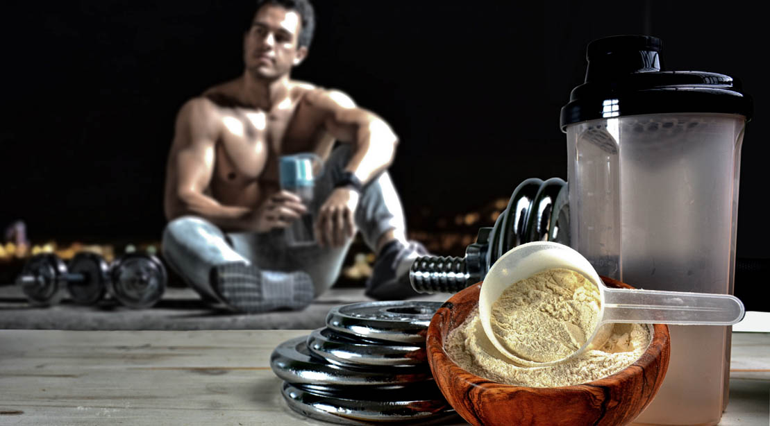 Lean and fit model resting and drinking a protein shake with creatine supplementation and BCAAs in it after performing a training plan