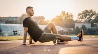 Fitness-Beginner-Wearing-A-Black-Shirt-Foam-Rolling-On-A-Running-Track