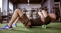 Male fitness enthusiast foam rolling in an empty gym