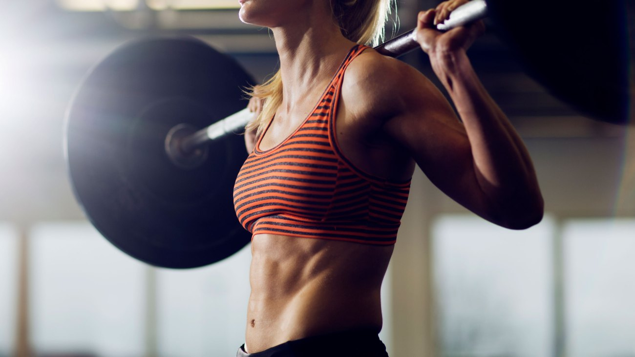 Woman Holding Barbell in Gym