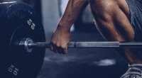 Man gripping a barbell for the barbell complex workout