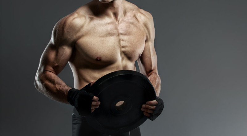 Lean and ripped man holding a workout plate doing plate curls exercise