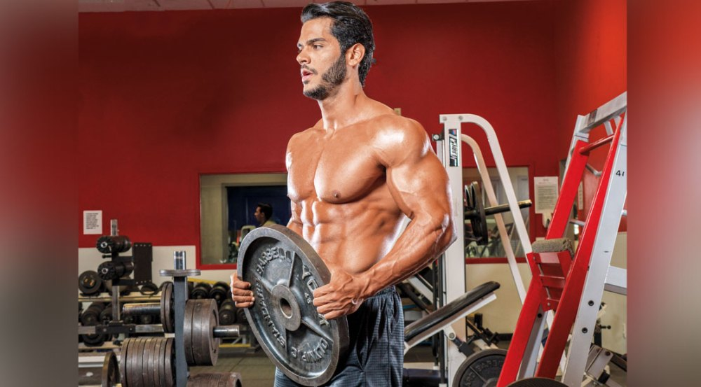 Fitness man holding a weight plate for his forearm workouts