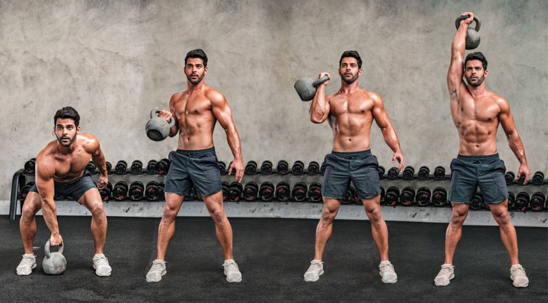 Muscular fitness model working out his arms with a single arm bottoms up kettlebell press exercise