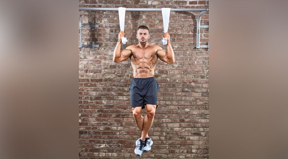 Muscular man doing forearms workout with a towel pullups exercise