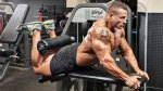 Bodybuilder doing workouts for legs with reverse leg curl exercise