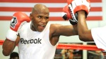 Floyd Mayweather training in the boxing ring against a trainer wearing mitts