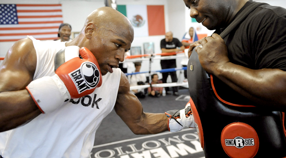 Boxer Floyd Mayweather training against a trainer wearing a body protector
