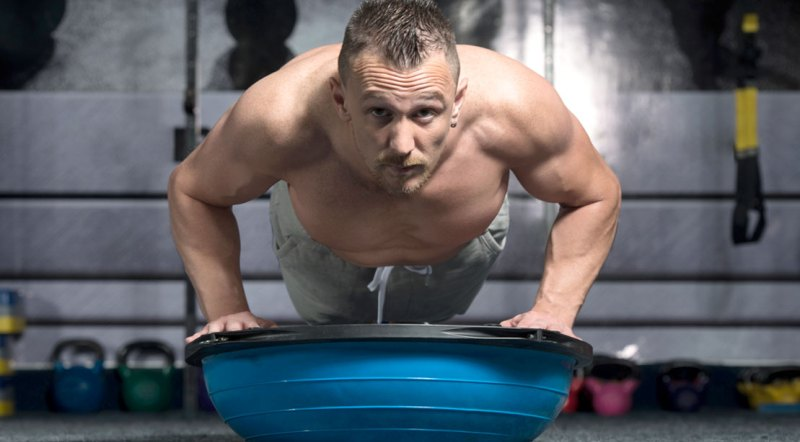 Muscular middle aged man working out the upper body with bosu ball pushup exercise
