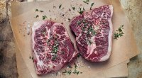A picture of steaks resting on a table.