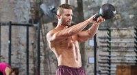 Худощавая мускулистая фитнес-модель, тренирующаяся с упражнением с гирями