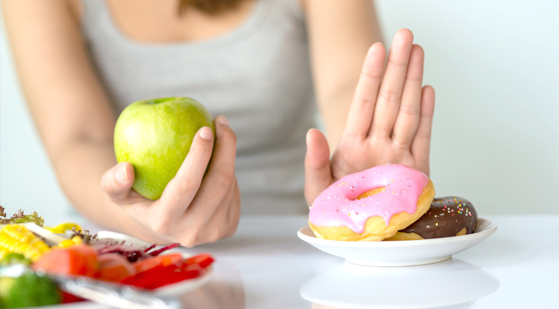 Female eating an apple while pushing away a plate of unhealthy foods.