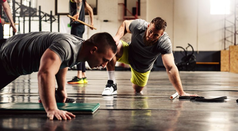 Personal Trainer motivating his client to do more pushups