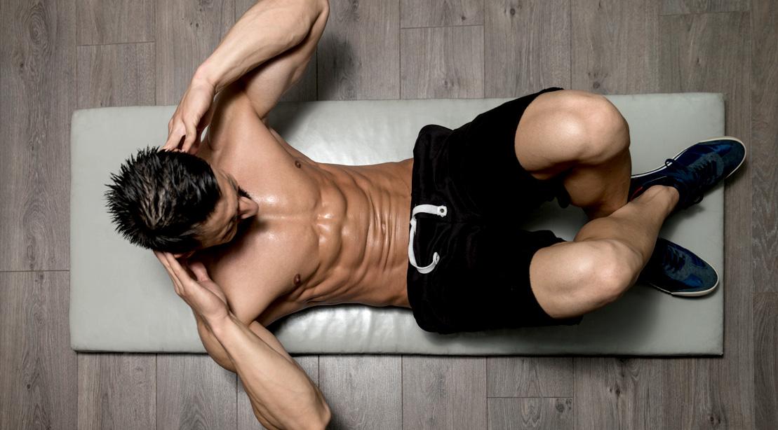 Ariel shot of man doing abs workout crunches on yoga mat