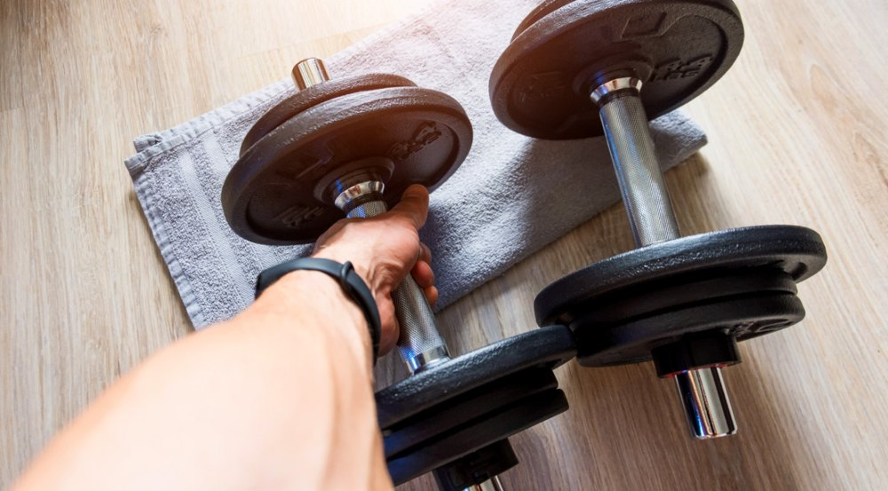 Man holding preparing a forearm workouts with dumbbell towel curl.