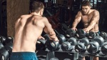 Muscular fitness model looking in the mirror next to the dumbbell rack