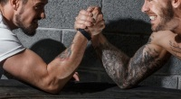 Two men with muscular forearms arm wrestling