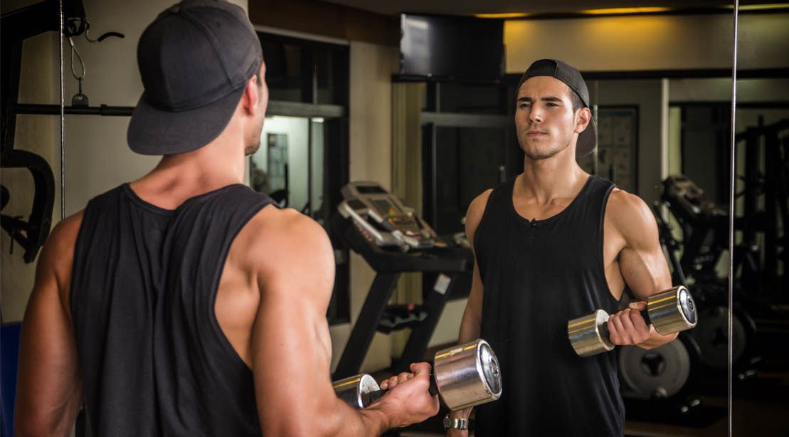 Young fit male doing upper arm workout with a bicep curl exercise in front of a mirror