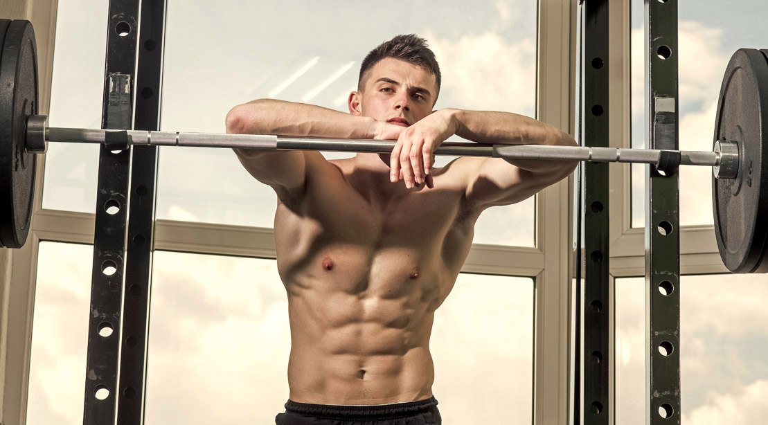Young muscular fitness model standing in the barbell bench
