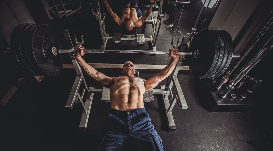 Bald bodybuilder doing chest workout with a barbell bench press