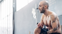 Portrait of tattooed man in gym looking away